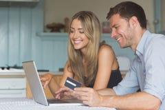 Couples mignons utilisant l'ordinateur portable ensemble à faire des emplettes en ligne Photos stock