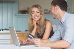Couples mignons utilisant l'ordinateur portable ensemble à faire des emplettes en ligne Photographie stock