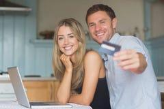 Couples mignons utilisant l'ordinateur portable ensemble à faire des emplettes en ligne Image stock