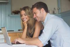 Couples mignons utilisant l'ordinateur portable ensemble Images stock