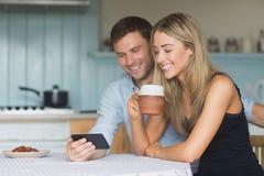 Couples mignons utilisant le smartphone ensemble Image stock