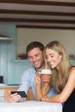Couples mignons utilisant le smartphone ensemble Images stock