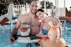 Couples millénaires adorables souriant tout en posant en anneaux en caoutchouc drôles Images stock