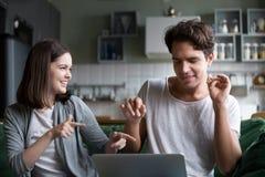 Couples millénaires ayant l'amusement écoutant la musique en ligne sur l'ordinateur portable Photos libres de droits