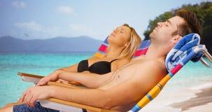 Couples millénaires blancs détendant sous le soleil à la plage Photographie stock libre de droits