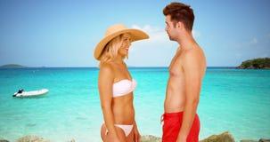 Couples millénaires blancs se tenant à profiter d'un agréable moment de plage Image libre de droits