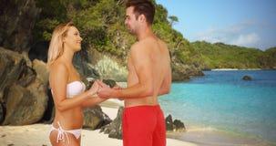 Couples millénaires dans l'amour tenant des mains et parlant sur la plage Photos stock