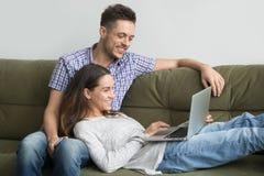 Couples millénaires de sourire appréciant à l'aide de l'ordinateur portable détendant sur le couc Image stock