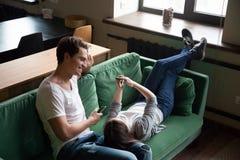 Couples millénaires de sourire parlant tenant des smartphones détendant o Photo libre de droits