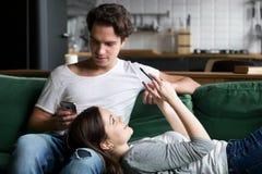 Couples millénaires hantés avec des smartphones vérifiant le netw social Photographie stock