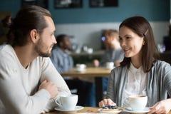 Couples millénaires heureux dans le flirt parlant d'amour à la table de café Image stock