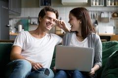 Couples millénaires heureux riant utilisant l'ordinateur portable ensemble sur le kitche Photos stock