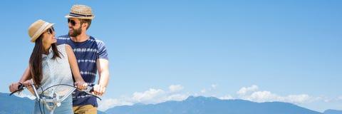 Couples millénaires sur la bicyclette contre les dessus et le ciel de montagne Photos stock