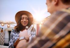 Couples millenial multi-ethniques flirtant tout en ayant une boisson sur le terrasse de dessus de toit au coucher du soleil Image stock