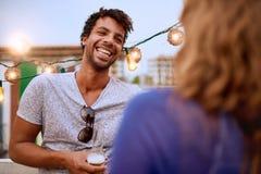 Couples millenial multi-ethniques flirtant tout en ayant une boisson sur le terrasse de dessus de toit au coucher du soleil Photographie stock libre de droits