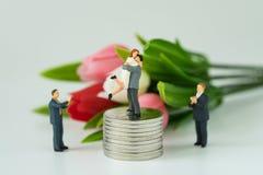 Couples miniatures se tenant sur la pile des pièces de monnaie et de tout autre W de applaudissement Photographie stock libre de droits
