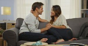 Couples mélangés affectueux parlant sur le divan Image libre de droits