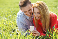 Couples with mobile phone in the park Royalty Free Stock Photo