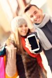 Couples montrant le smartphone tout en faisant des emplettes Photo stock