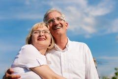 Couples mûrs heureux regardant au ciel bleu Image libre de droits