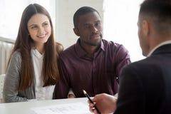 Couples multi-ethniques consultant le vrai agent immobilier sur la maison de achat Image libre de droits