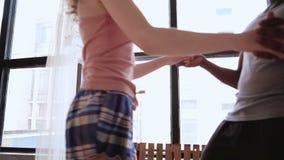 Couples multi-ethniques dans des pyjamas ayant l'amusement ensemble Homme africain et danse européenne de femme près de la grande banque de vidéos