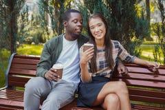 Couples multi-ethniques dans l'amour ayant le café dans le parc Images stock