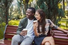 Couples multi-ethniques dans l'amour ayant le café dans le parc Photo libre de droits