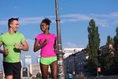 Couples multi-ethniques de sourire de jeunes pulsant dans la ville Photographie stock