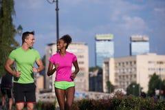 Couples multi-ethniques de sourire de jeunes pulsant dans la ville Images stock