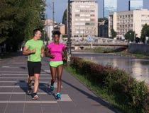 Couples multi-ethniques de sourire de jeunes pulsant dans la ville Photos stock