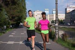 Couples multi-ethniques de sourire de jeunes pulsant dans la ville Image libre de droits