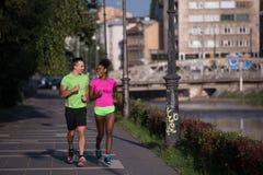 Couples multi-ethniques de sourire de jeunes pulsant dans la ville Photographie stock libre de droits