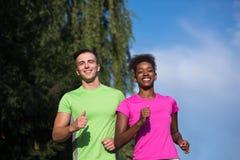 Couples multi-ethniques de sourire de jeunes pulsant dans la ville Photo stock