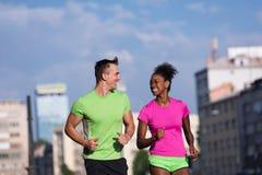 Couples multi-ethniques de sourire de jeunes pulsant dans la ville Photos libres de droits