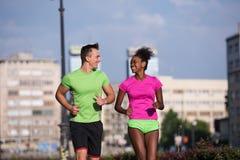Couples multi-ethniques de sourire de jeunes pulsant dans la ville Images libres de droits