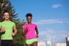 Couples multi-ethniques de sourire de jeunes pulsant dans la ville Image stock