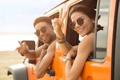 Couples multi-ethniques de sourire se reposant dans une voiture Photographie stock libre de droits