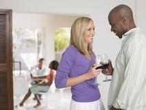 Couples multi-ethniques grillant des verres à vin Photo stock