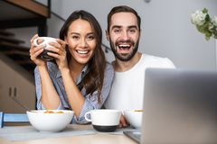 Couples multi-ethniques heureux prenant le petit d?jeuner photos libres de droits