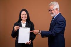 Couples multi-ethniques mûrs d'affaires sur le fond brun Photos stock