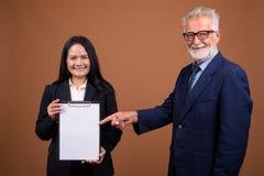 Couples multi-ethniques mûrs d'affaires sur le fond brun Image stock