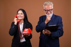 Couples multi-ethniques mûrs d'affaires sur le fond brun Photographie stock