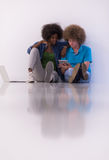 Couples multi-ethniques se reposant sur le plancher avec un ordinateur portable et un comprimé Images libres de droits