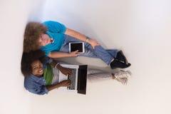Couples multi-ethniques se reposant sur le plancher avec un ordinateur portable et un comprimé Photos libres de droits