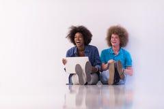 Couples multi-ethniques se reposant sur le plancher avec un ordinateur portable et un comprimé Image libre de droits