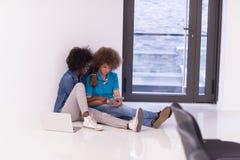 Couples multi-ethniques se reposant sur le plancher avec un ordinateur portable et un comprimé Photo libre de droits
