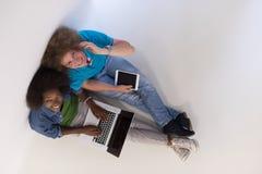 Couples multi-ethniques se reposant sur le plancher avec un ordinateur portable et un comprimé Photos stock