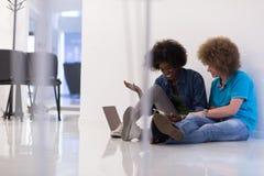 Couples multi-ethniques se reposant sur le plancher avec un ordinateur portable et un comprimé Photo stock