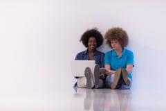 Couples multi-ethniques se reposant sur le plancher avec un ordinateur portable et un comprimé Image stock